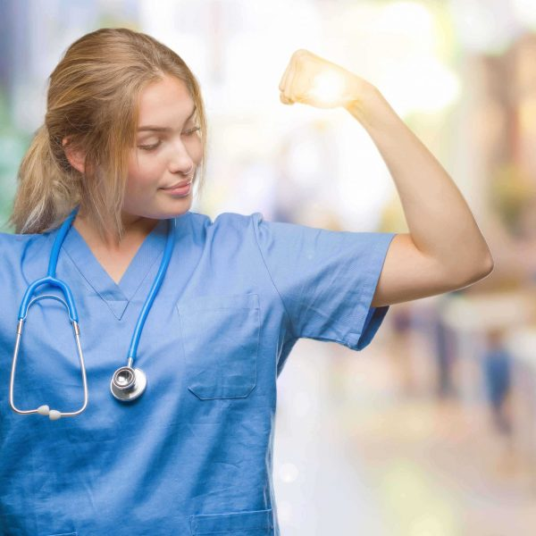 Young caucasian doctor woman wearing surgeon uniform over isolated background showing arms muscles smiling proud. Fitness concept.