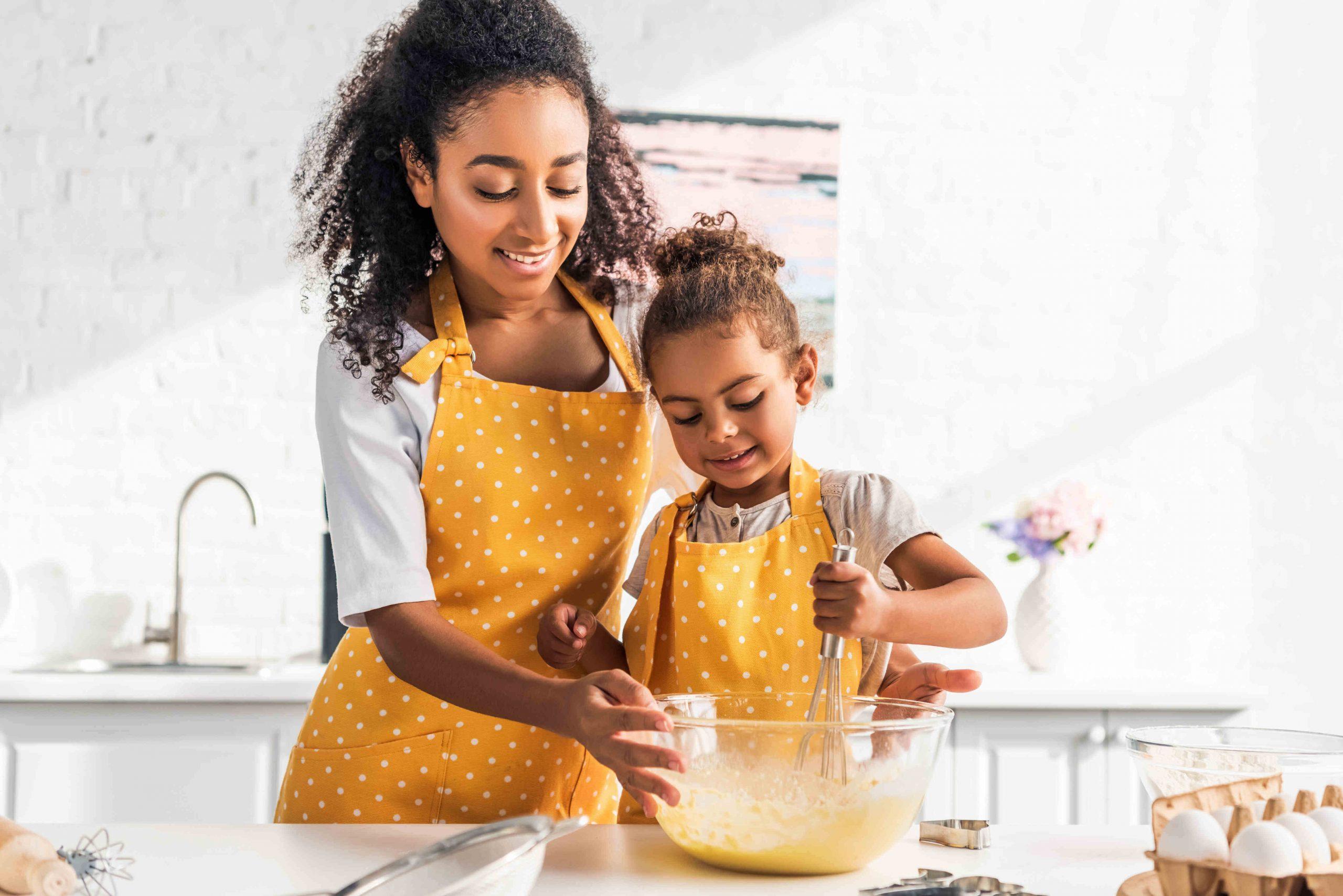 Moeder met kind hebben plezier tijdens bakken